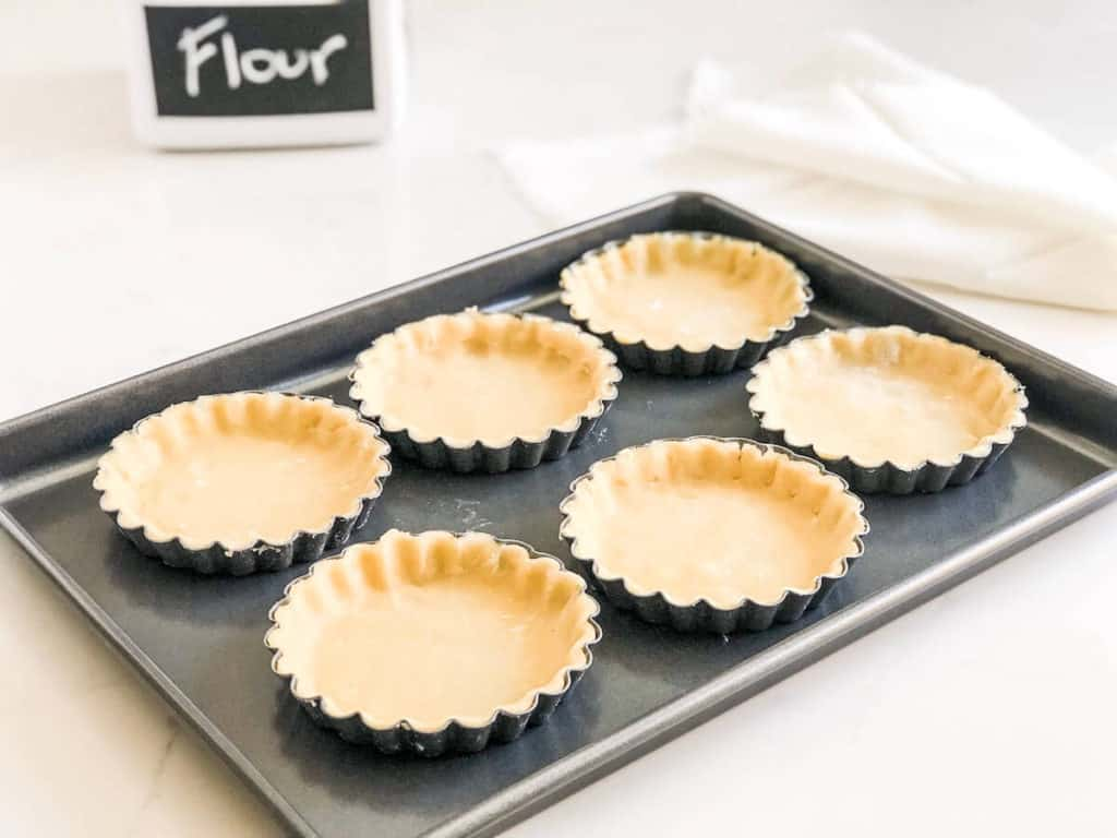 unbaked mini tarts on baking sheet
