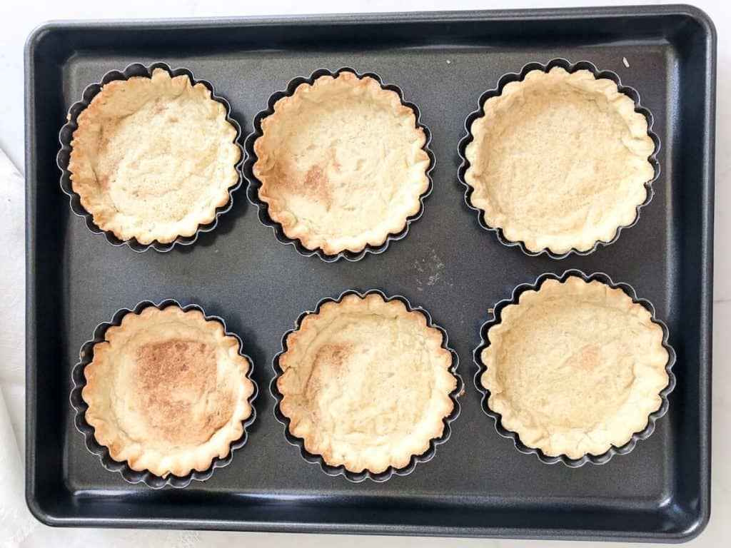baked mini tarts on a baking sheet