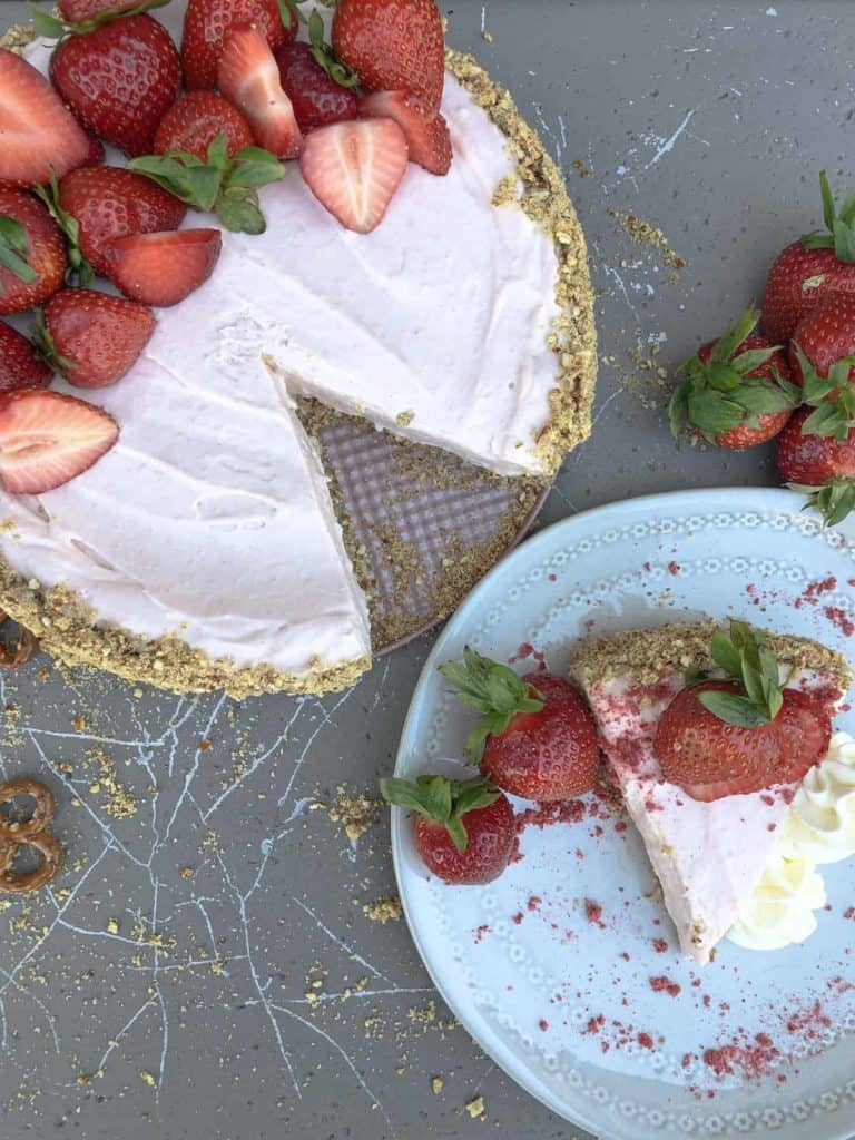 Whole Strawberry Frozen Cheesecake with slice on plate