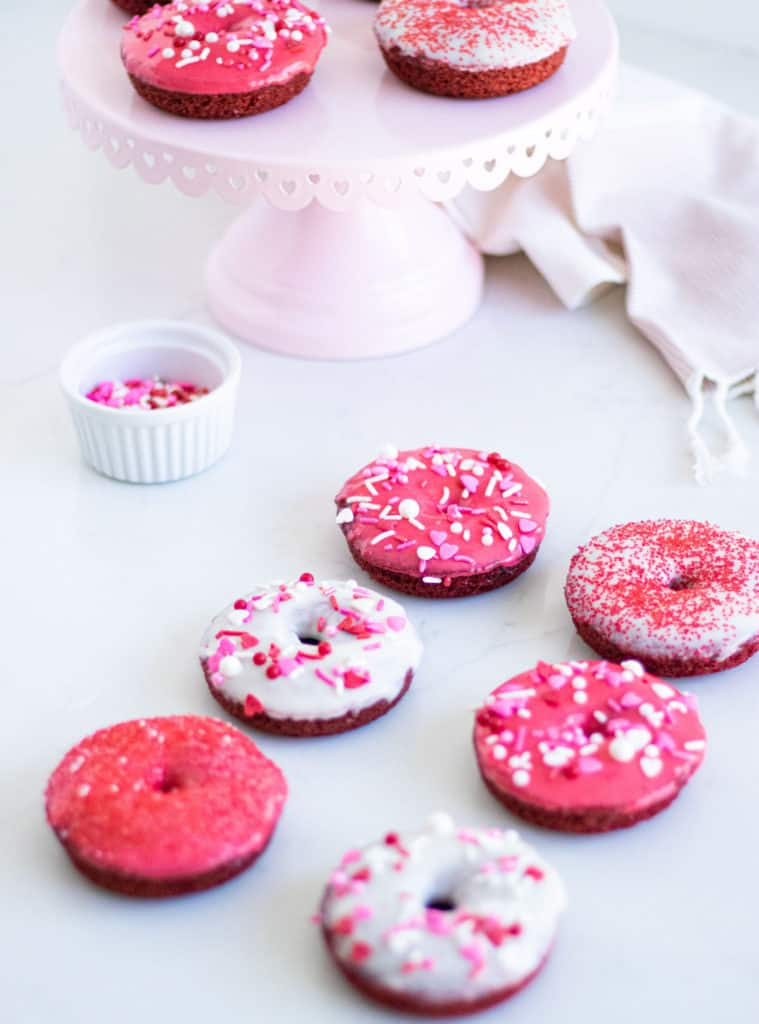 red and white donuts with sprinkles on a counter