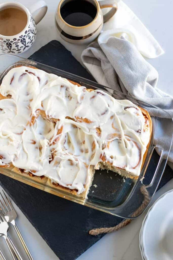 pan of apple cinnamon rolls with cups of coffee