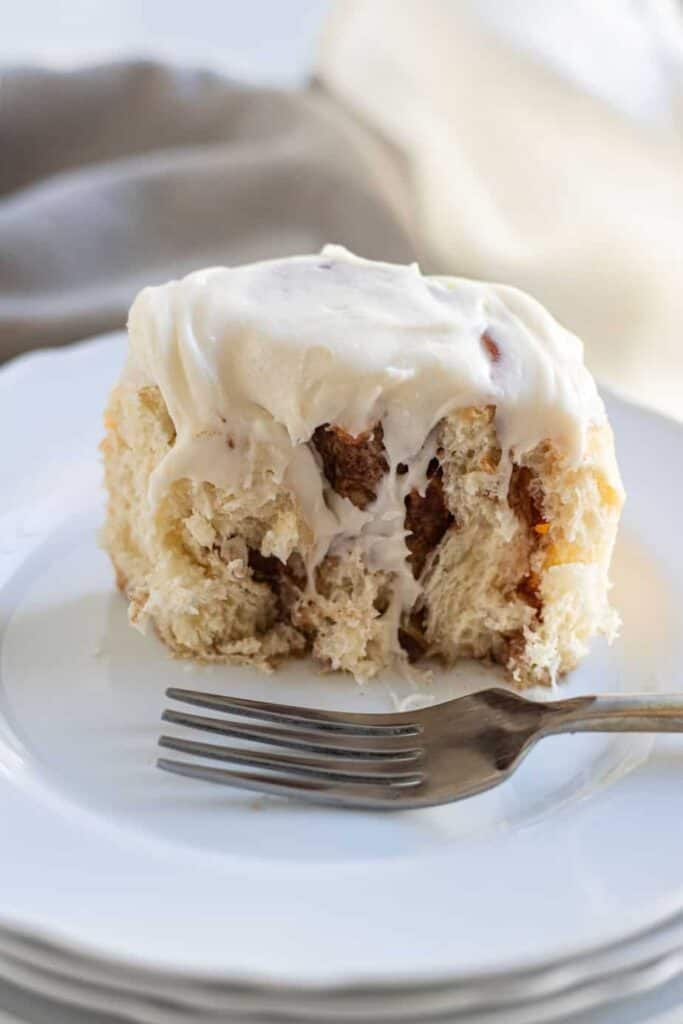 close up of apple cinnamon roll cut in half on plate