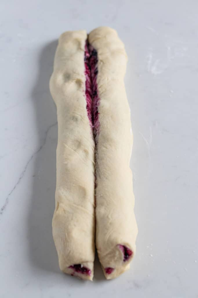 Rolled blueberry cream cheese babka dough cut in half