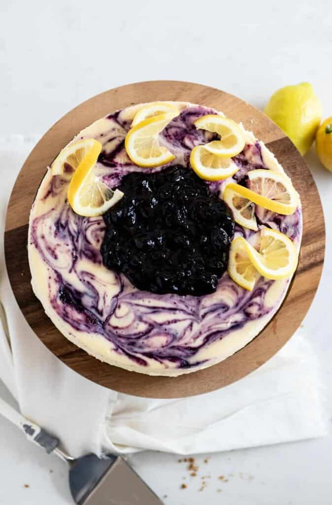 overhead view of lemon blueberry cheesecake on cake stand