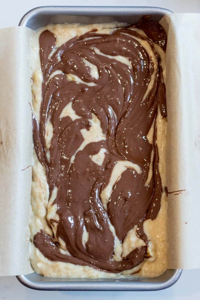 swirls of nutella on top banana bread batter