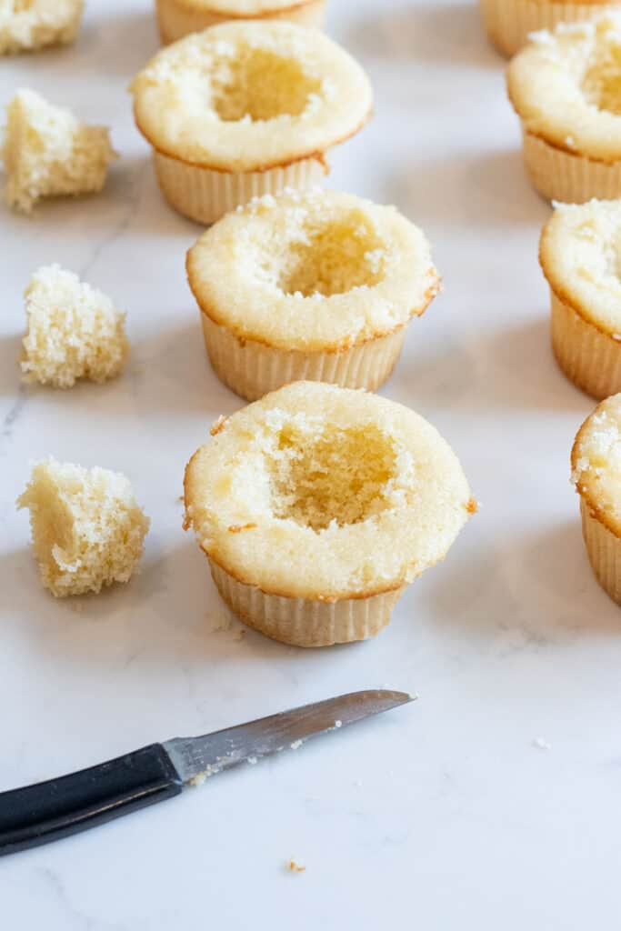vanilla cupcakes with hole cut out of middle
