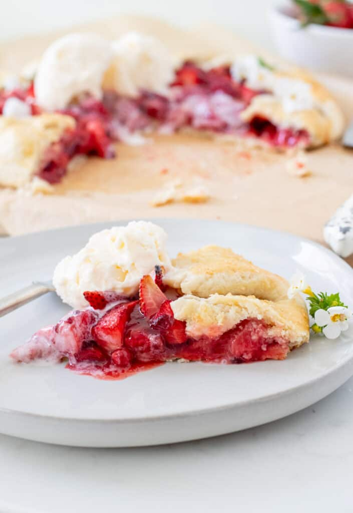 slice of strawberry galette with vanilla ice cream on a plate