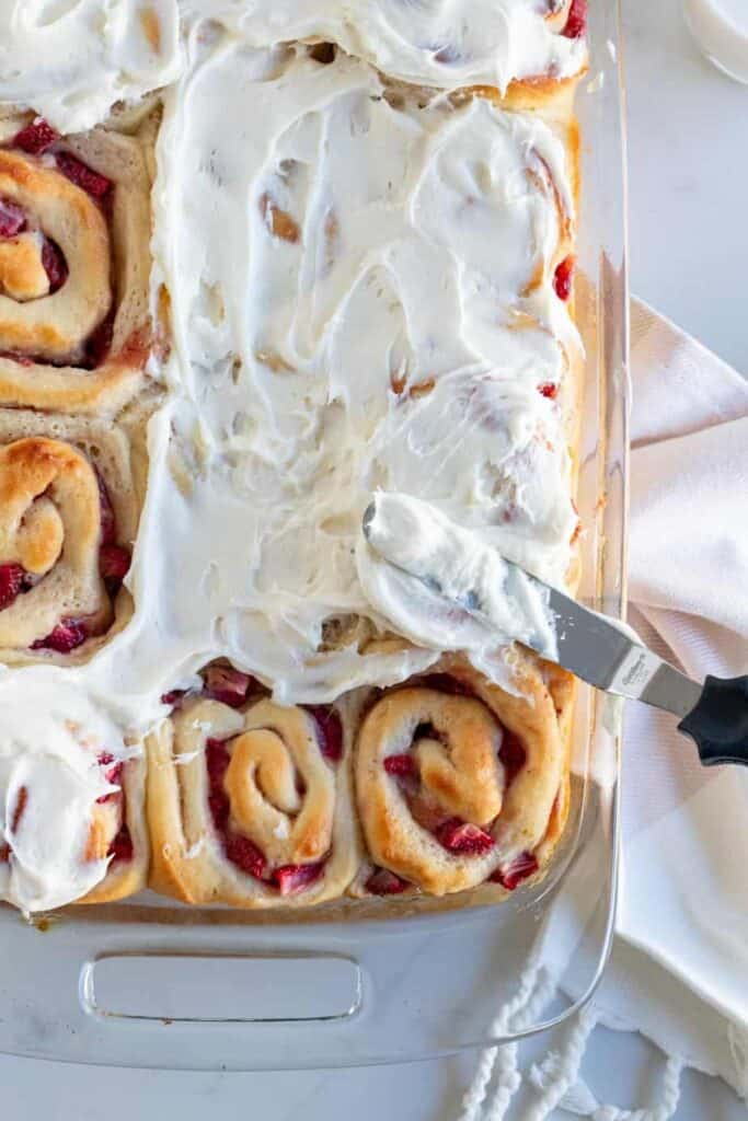 pan of strawberry rolls being frosted with cream cheese frosting
