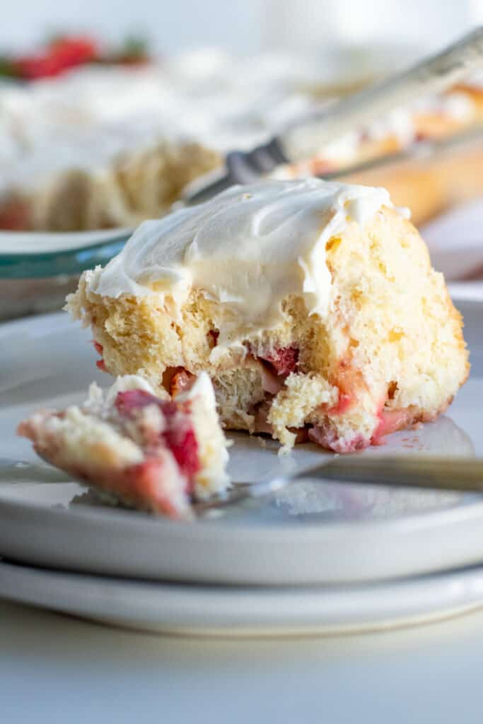 close up of a strawberry sweet roll with bite on fork