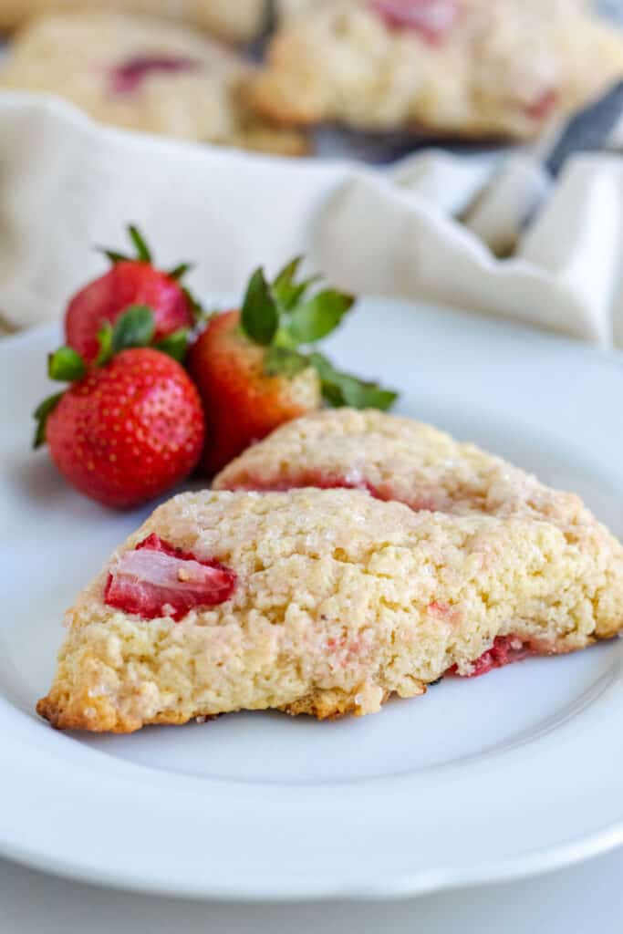 up close view of strawberry scone on a plate with strawberries