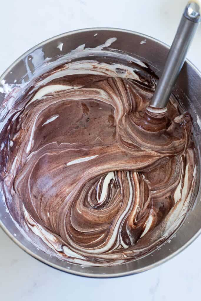 chocolate no-churn ice cream being stirred in metal bowl