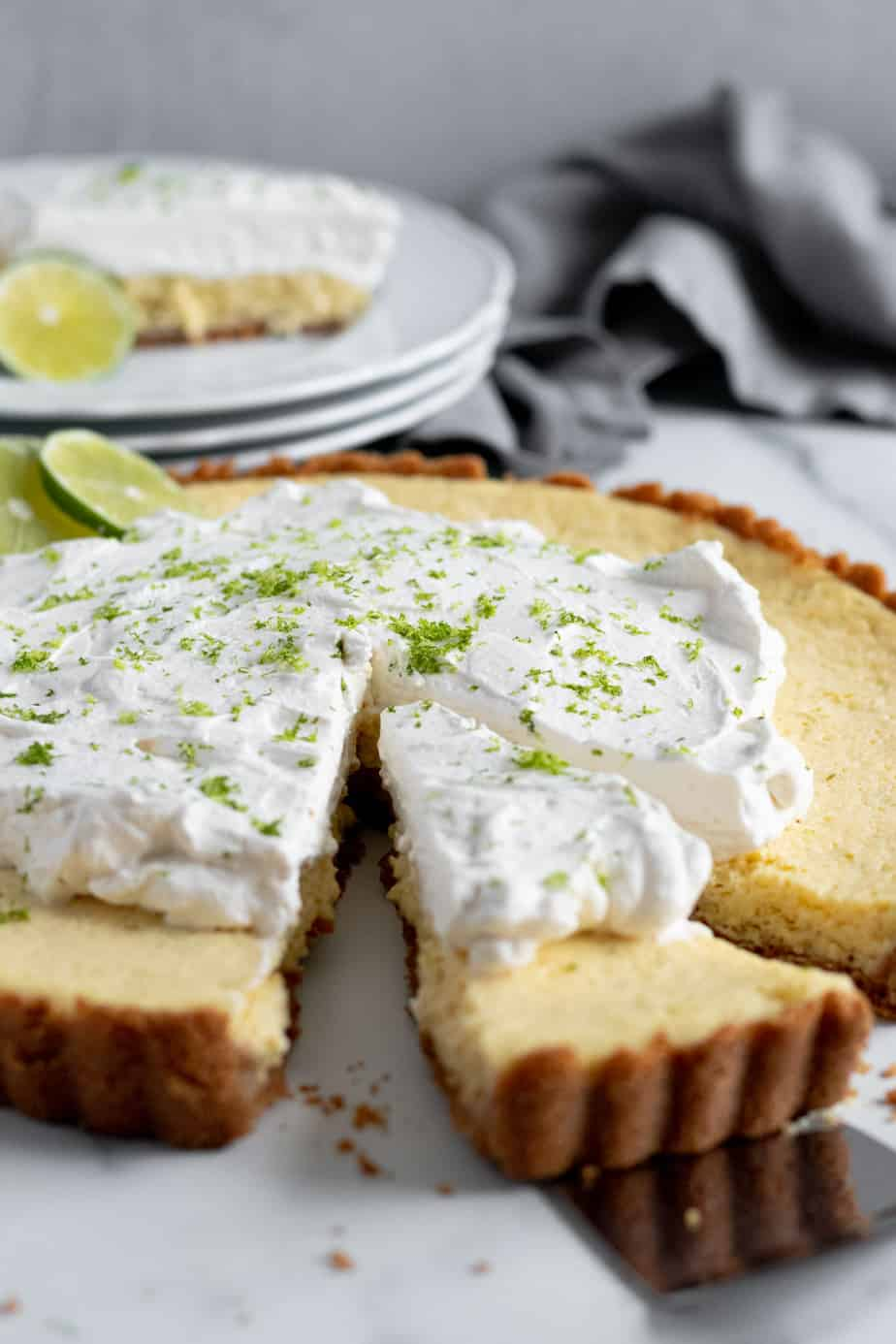 slice of key lime tart cut out of large tart