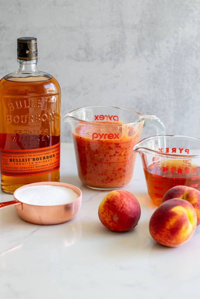 Bourbon, peach puree, peaches and sugar on counter