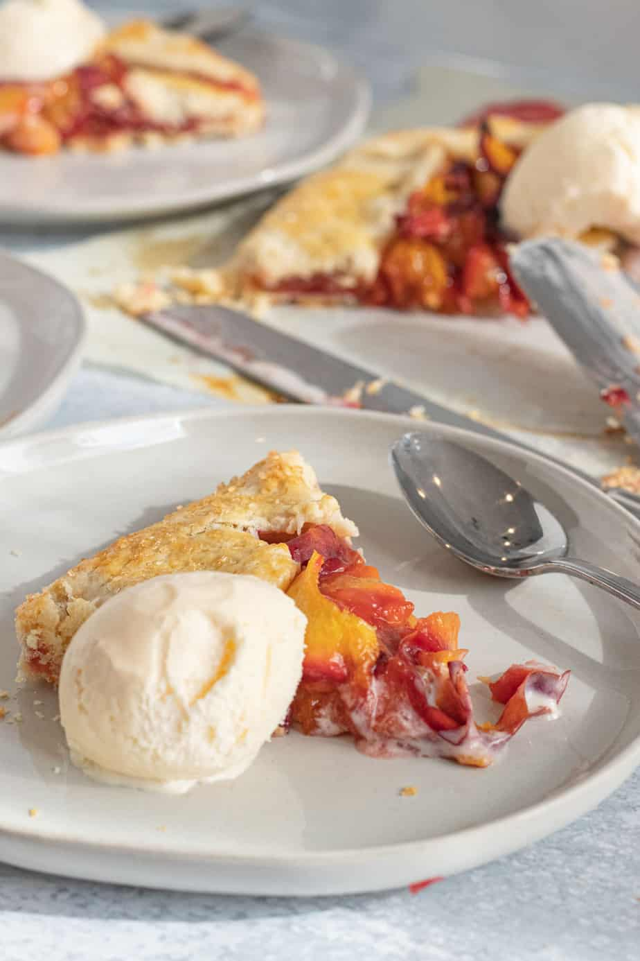 slice of peach galette on plate with vanilla ice cream