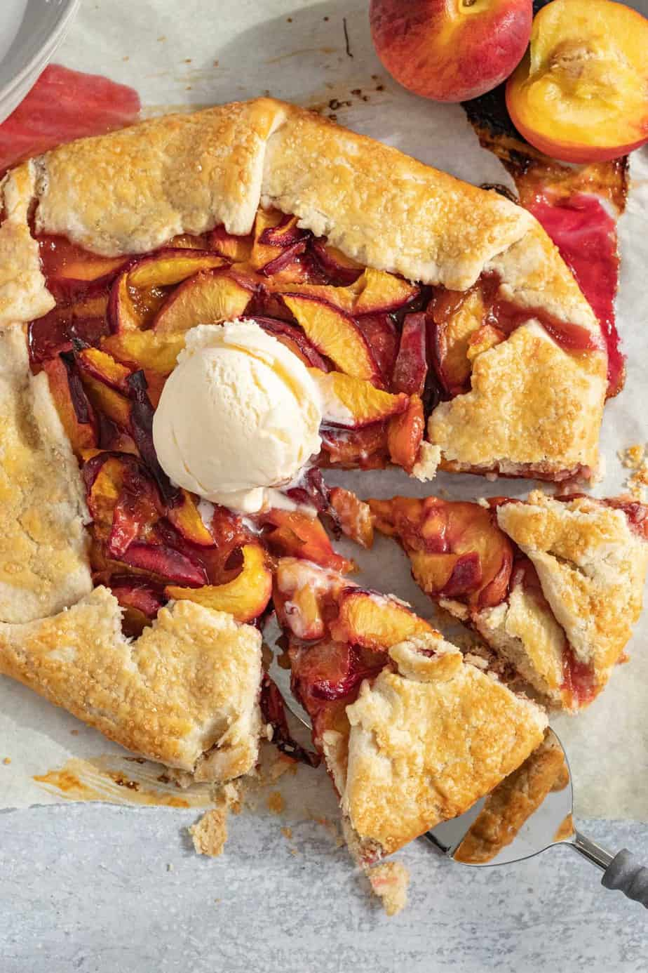 galette with peaches with 2 slices cut out and a scoop of vanilla ice cream on top