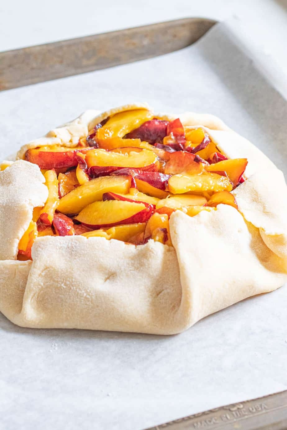 Uncooked peach galette on baking sheet