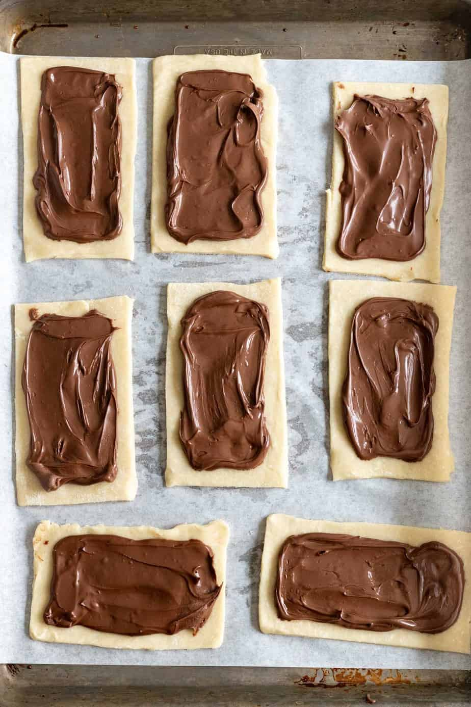 nutella spread on 8 dough rectangles on a baking sheet lined with parchment