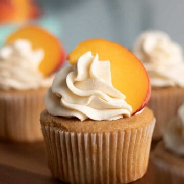Peach cobbler cupcake with a fresh peach on top on a wood serving platter