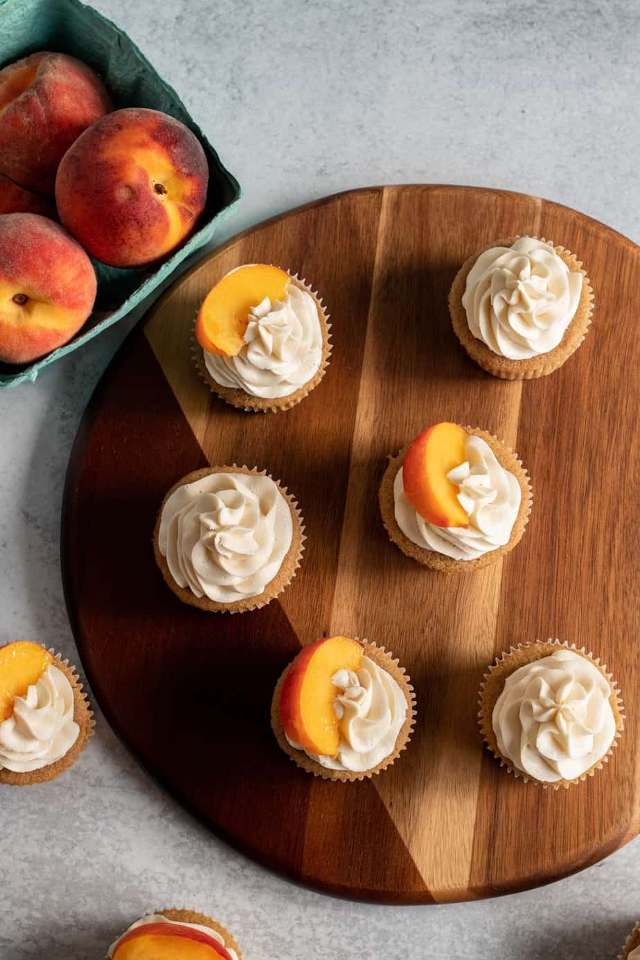 overhead view of cupcakes with vanilla frosting and peach slices on top on a wooden board
