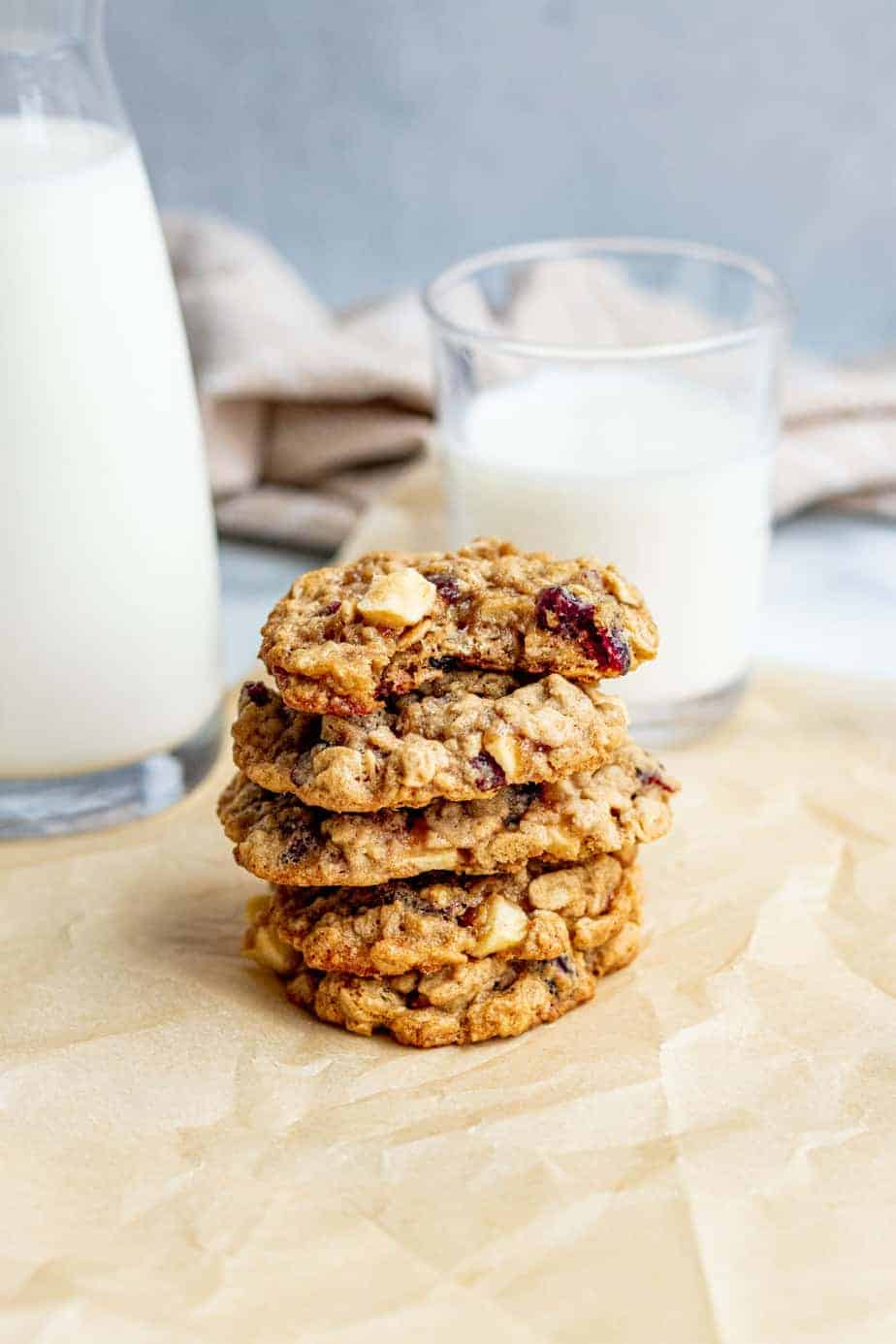 stack of apple oatmeal cookies with glasses of milk in background
