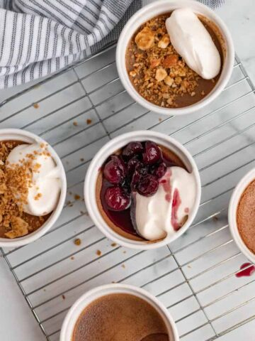 chocolate pots de cremes in white ramekins with pretzel crumble or bourbon cherries on top