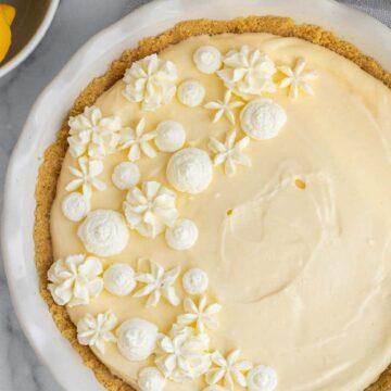 lemon cream pie in a white pie dish next to bowl of lemons