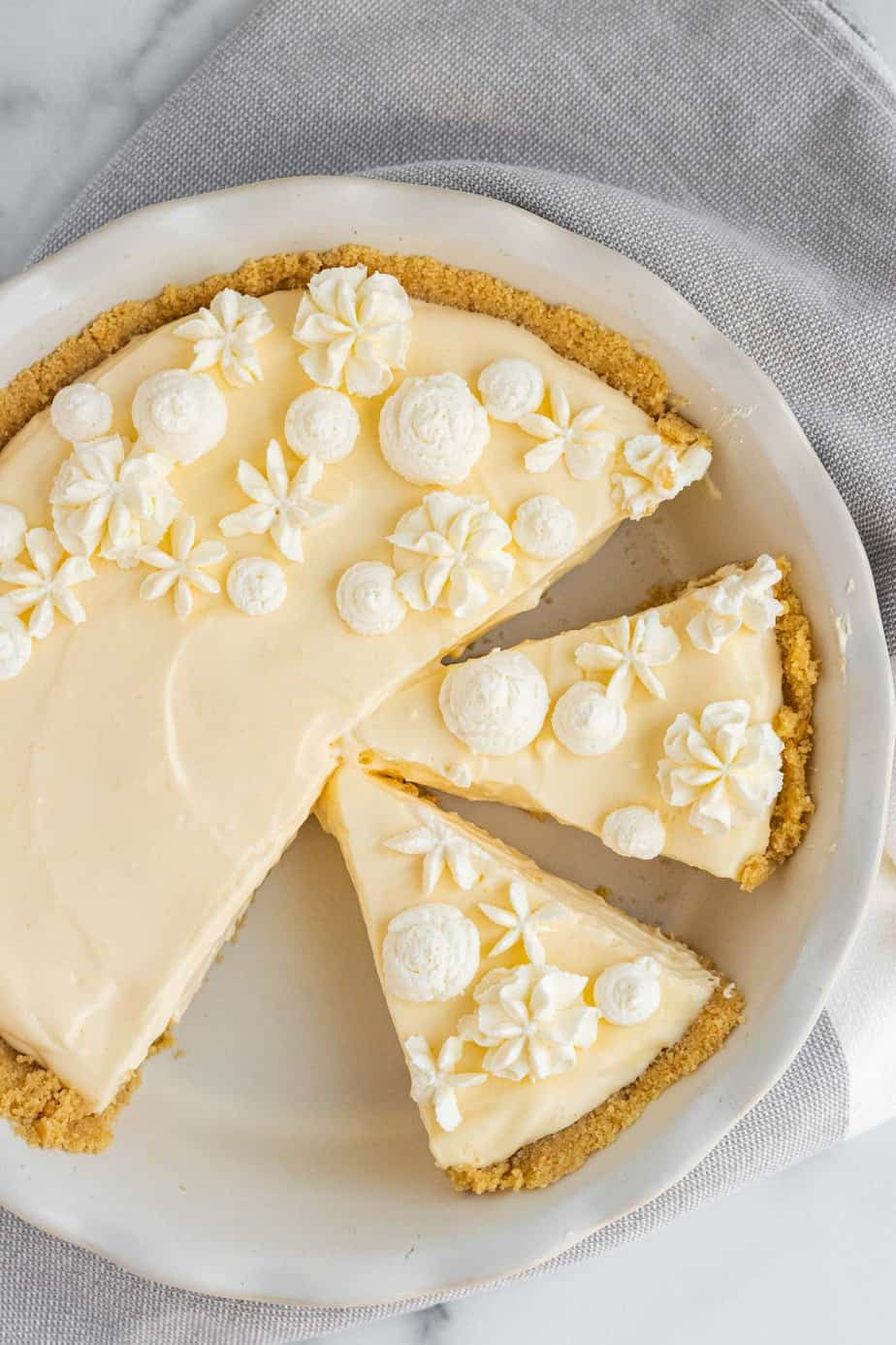 lemon cream pie with whipped cream decorations in white pie dish with 2 slices cut from pie