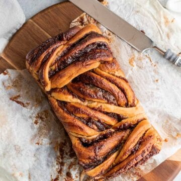 apple cinnamon babka on parchment paper on top of a round wood cutting board