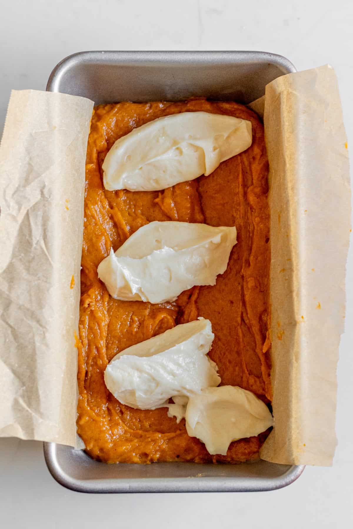dollops of cream cheese on top of pumpkin bread batter in a loaf pan