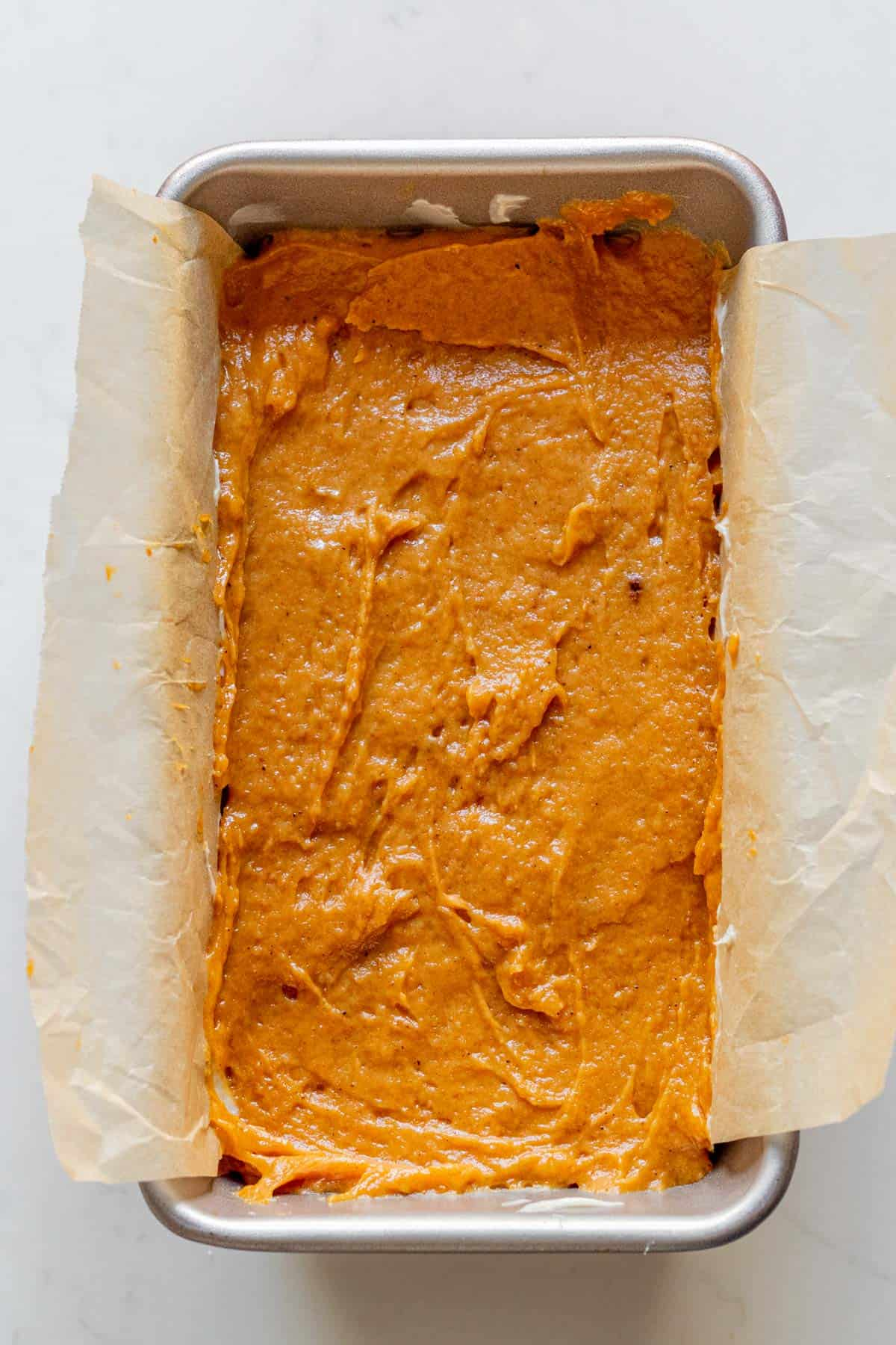 pumpkin bread batter in a loaf pan