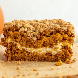 close up of loaf of pumpkin bread cut open showing cream cheese layer