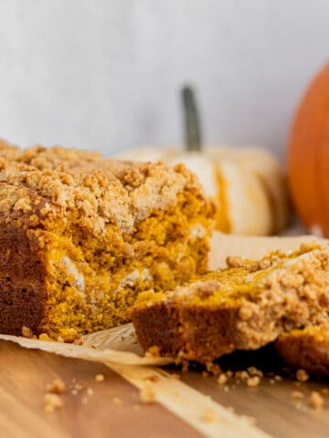 loaf of pumpkin cream cheese bread sitting on a wood cutting board with 2 slices cut. 2 pumpkins in the background.