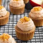 apple pie cupcakes with apple pie filling on top sitting on a wire cooling rack with apple in background