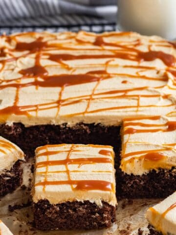 slices of chocolate sheet cake with salted caramel frosting drizzled with salted caramel with milk in glass