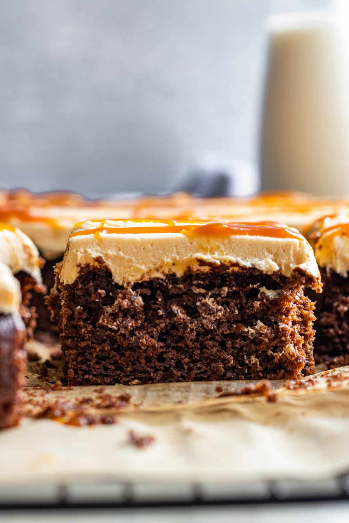 slice of chocolate cake with salted caramel frosting and caramel drizzle on top. Glass of milk in background.