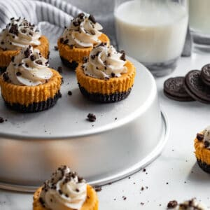 mini pumpkin cheesecakes with whipped cream sitting on silver tin with cookies and milk in the background