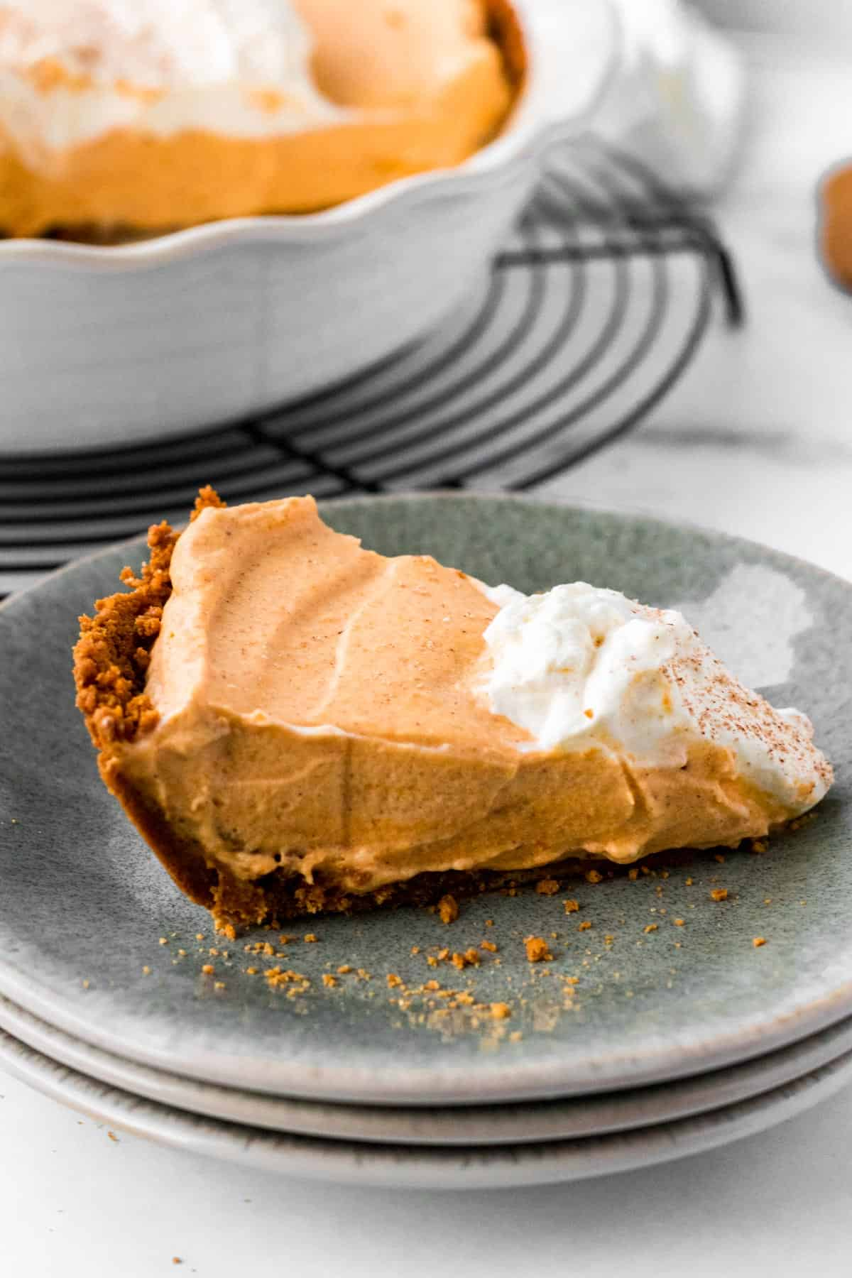 slice of pumpkin mousse pie on stack of plates with full pie in background