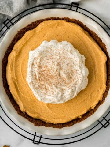 pumpkin mousse pie in white pie dish on black cooling rack with pie server and gingersnap cookies