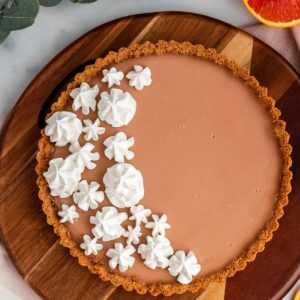 blood orange tart with meringue on a wood platter with oranges around it