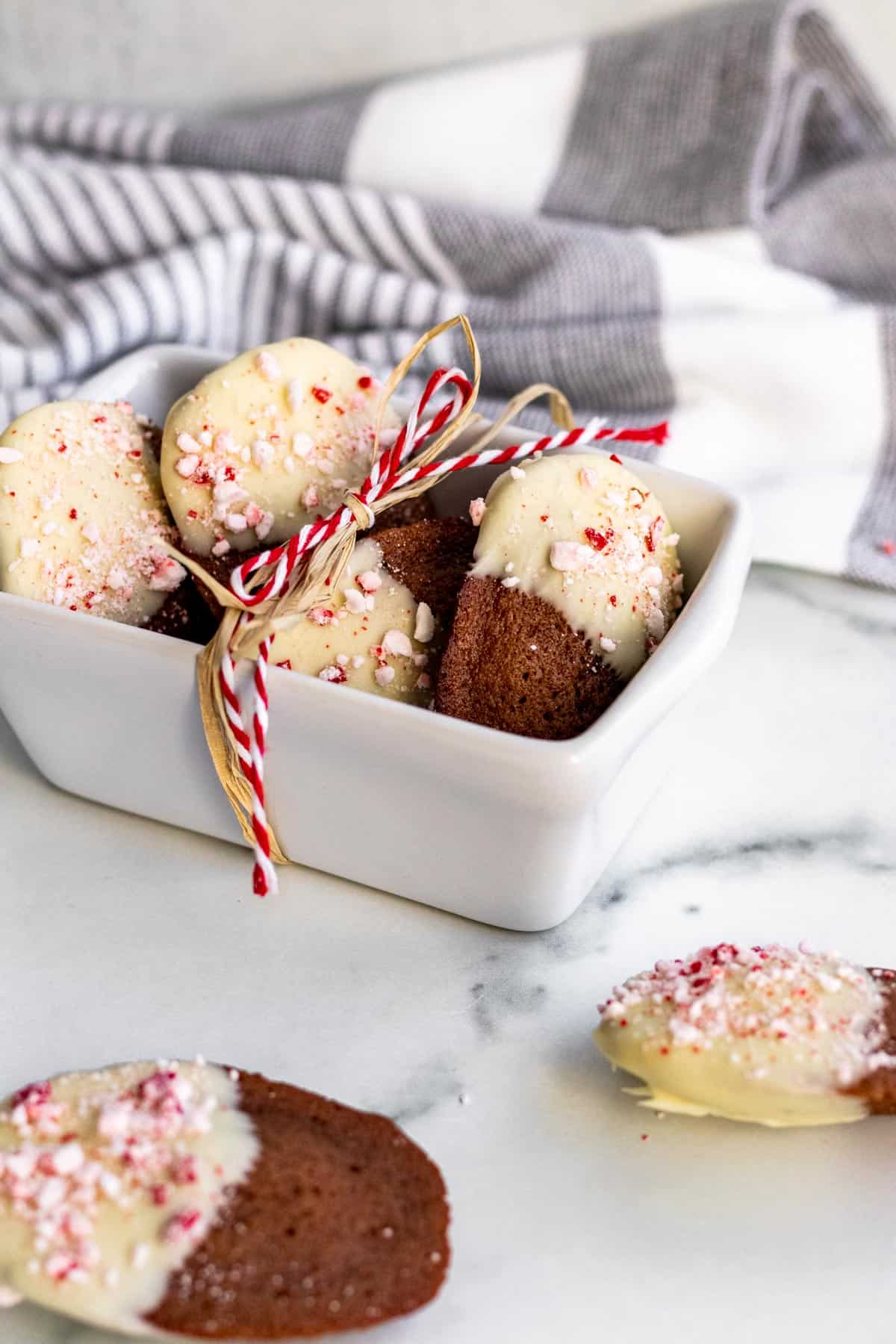 white mini ceramic bread pan with chocolate madeleines dipped in white chocolate and peppermint candies