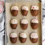 Cookie sheet with chocolate madeleines dipped in white chocolate and sprinkled with peppermint candies