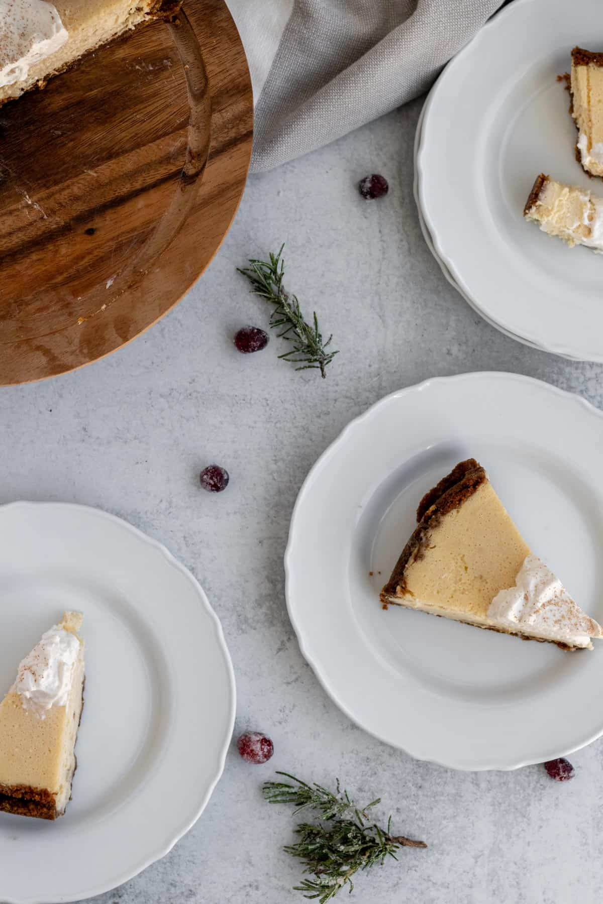 white plates with cheesecake slices on them and scattered rosemary sprigs and cranberries
