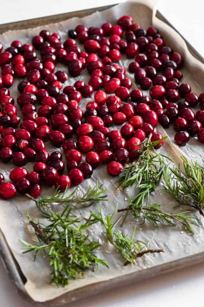 cranberries and rosemary on a parchment lined baking tray