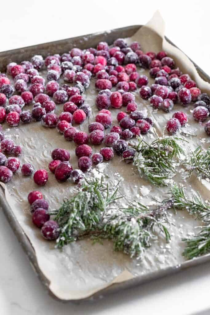 sugared cranberries and rosemary on a parchment lined baking tray