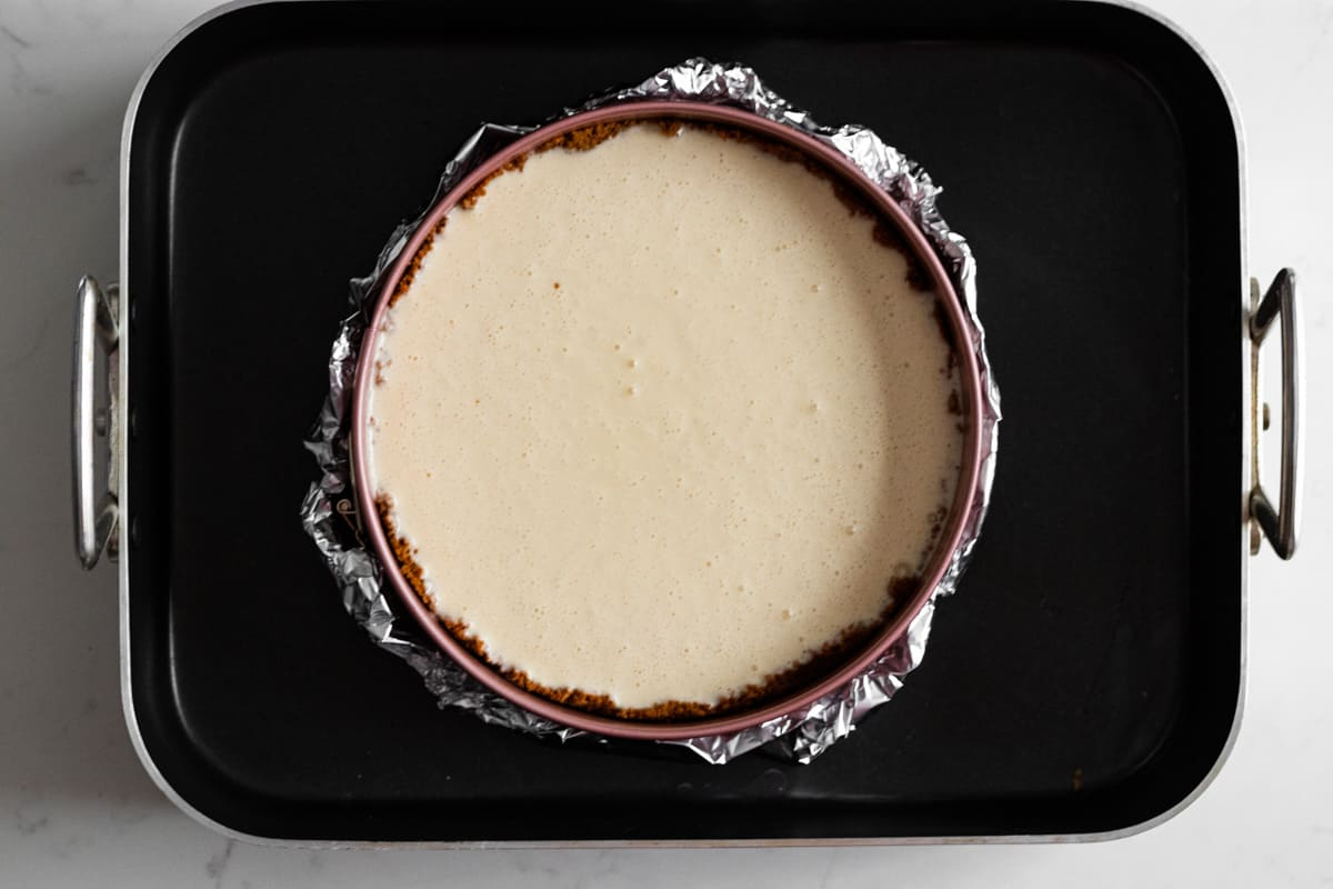 unbaked cheesecake batter in springform pan wrapped in foil and set in a roasting pan