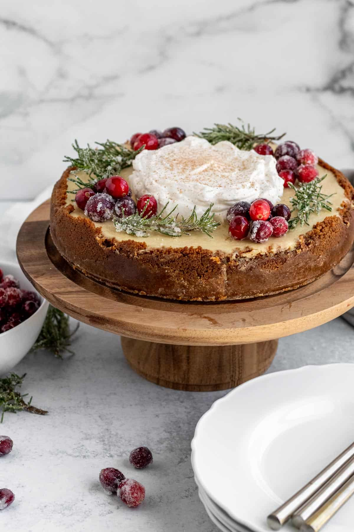 eggnog cheesecake with whipped cream, sugared cranberries and rosemary on a wood cake pedestal with a stack of plates