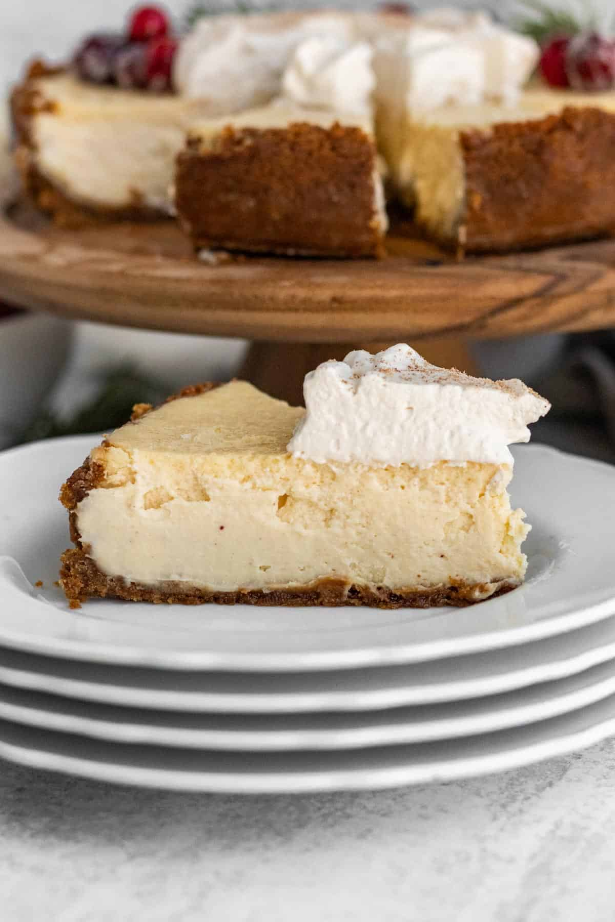slice of eggnog cheesecake with whipped cream on a stack of white plates with the full cheesecake in the background