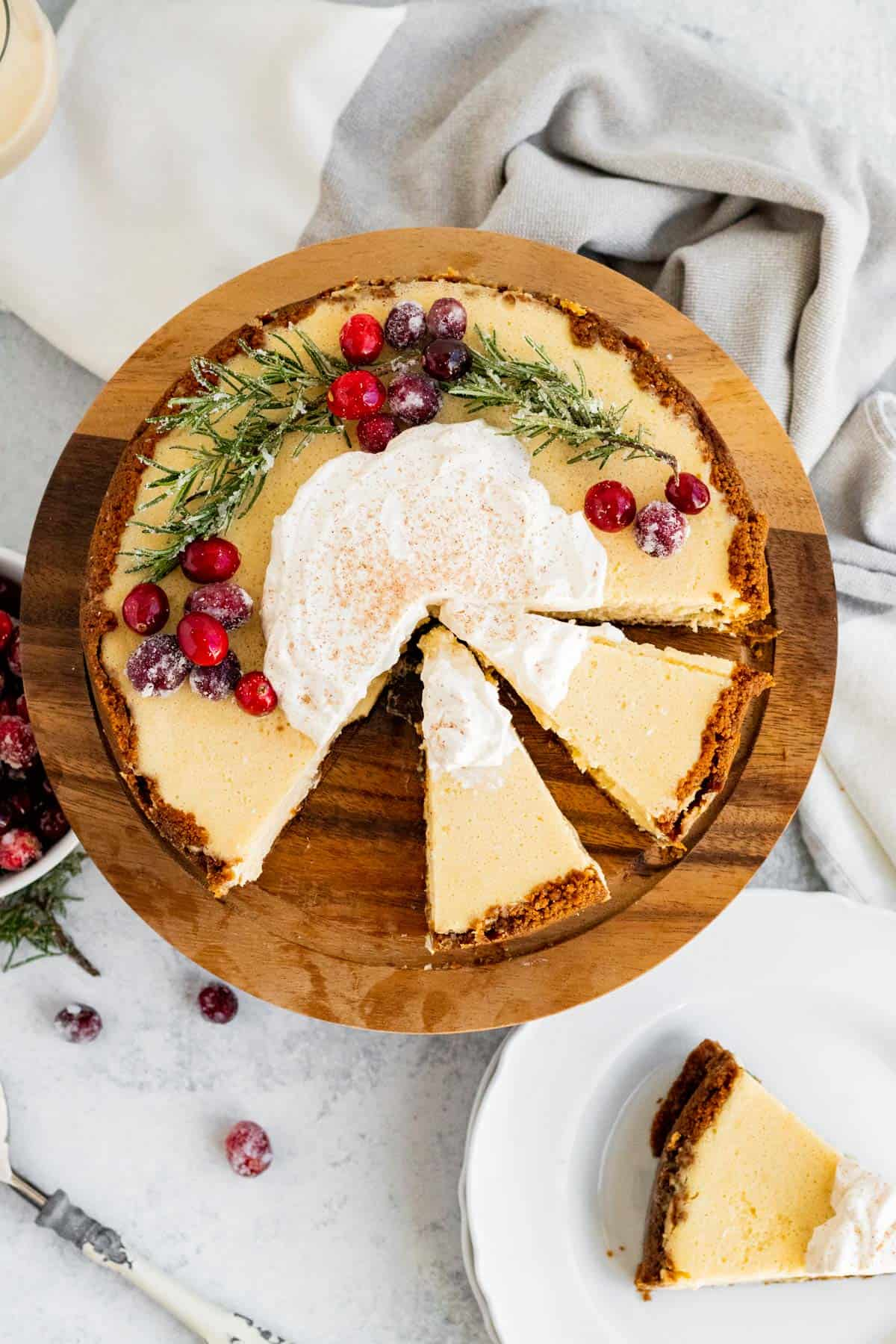 overhead view of an eggnog cheesecake decorated with cranberries and rosemary and 2 slices sliced on a wood cake stand