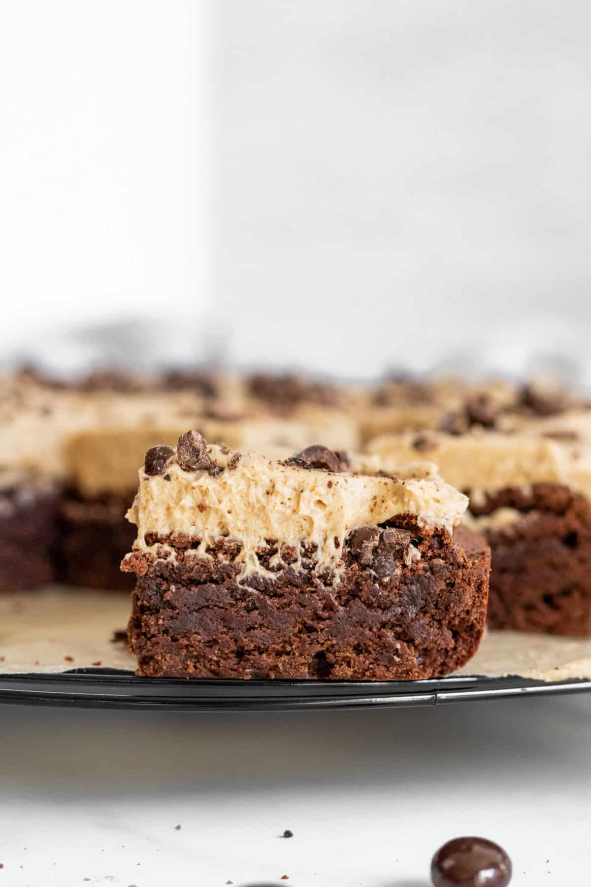 close up of a slice of brownie with espresso frosting on a cooling rack with other brownies in the background