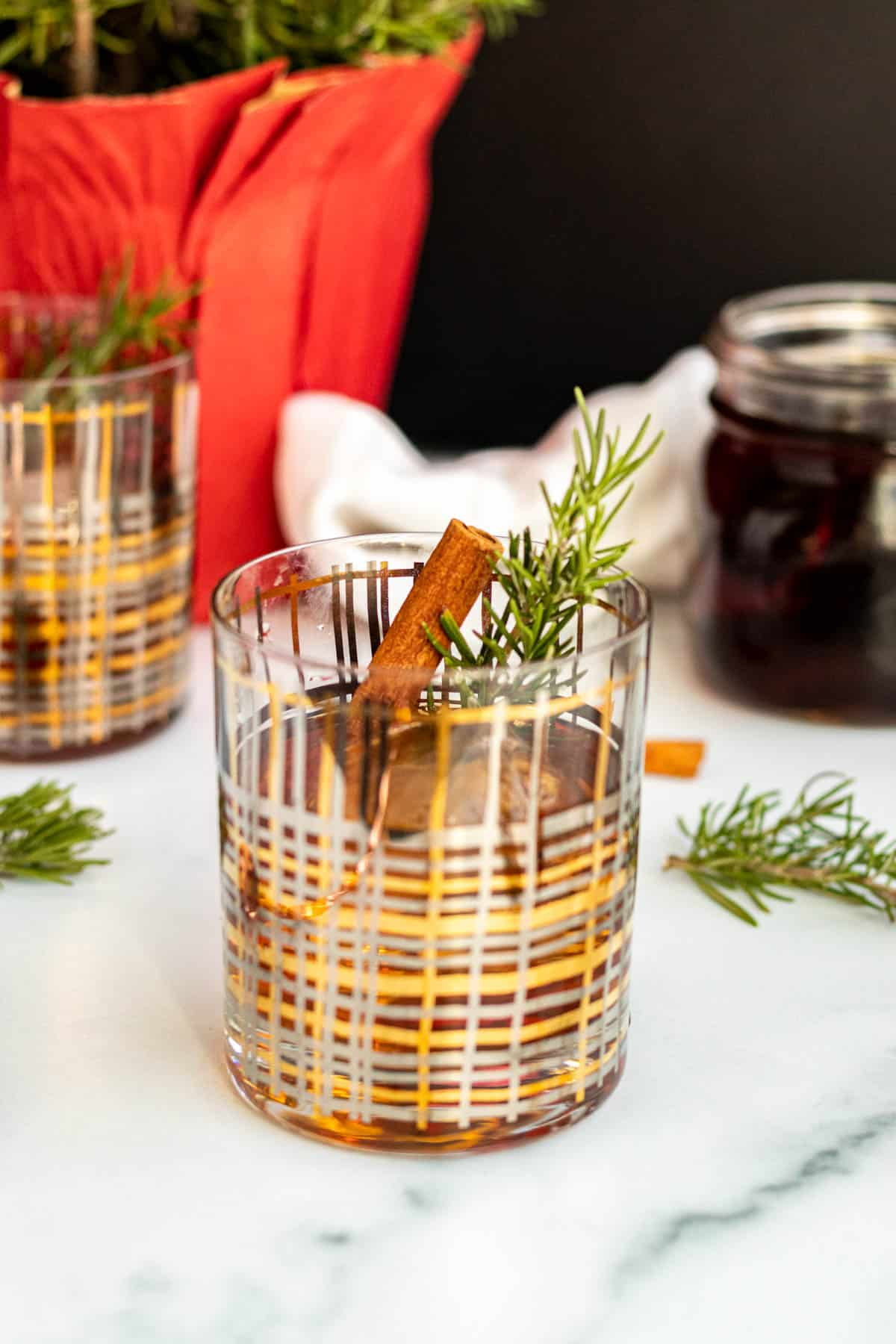 winter old fashioned cocktail in a gold and silver striped rocks glass with rosemary sprigs scattered around